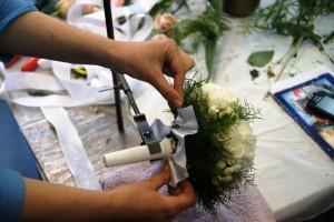 Florysta przy pracy nad bukietem ślubnym