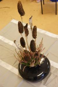 Dekoracja florystyczna w naczyniu z szyszkami