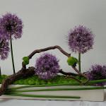 Fioletowe kwiaty z zielonym santini w naczyniu