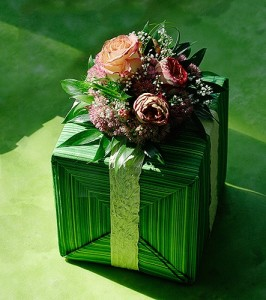 Pakowanie prezentu w zielony papier z ozdobą kwiatową