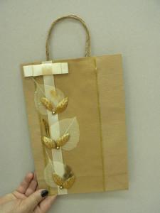 papierowa torba na prezent ze złotymi ozdobami