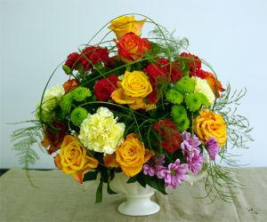 Bukiet dekoracyjny w naczyniu z różami, goździkami i zielonym santini