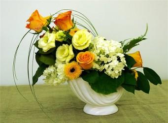 Kompozycja kwiatowa w naczyniu żółto-pomarańczowa