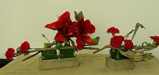 Kompozycja dekoracyjna z czerwonych kwiatów w naczyniu